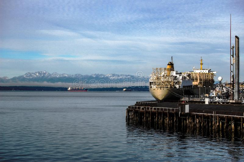 Container Ship Port of Seattle Washington Puget Sound. Cargo container ship docked at Seattle Port. Snow capped Olympic Mountains in background. Tourist cruise royalty free stock images