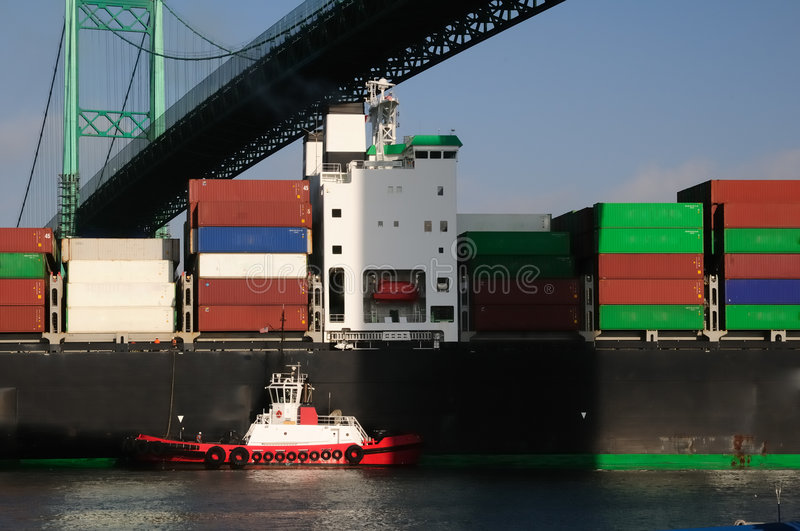Container ship and red tugboat stock photography