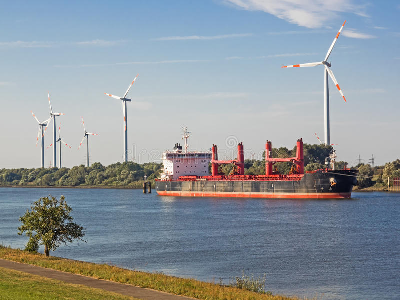 Container ship on a river with wind turbines in the background. Empty freighter on river Weser with wind power plants onshore royalty free stock photos