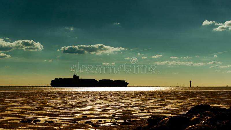Container ship silhouette against the sunset. Container ship silhouette on the horizon against the glow of the setting sun stock image