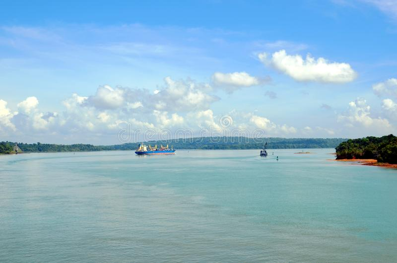 Container ship transiting through Panama Canal. Container ship transiting through Panama Canal on a sunny day, beautiful day, view on the Gatun Lake royalty free stock image