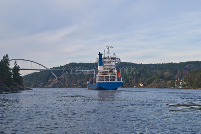 Container ship under svinesund bridge, image 16. While i'm under svinesund bridge (which is a bridge that borders between norway and sweden) shows the container royalty free stock photography
