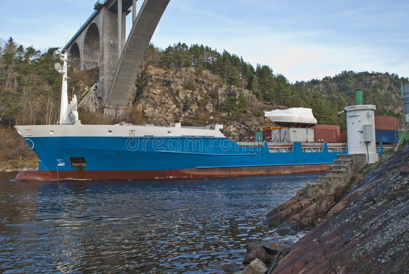 Container ship under svinesund bridge, image 2. While i'm under svinesund bridge (which is a bridge that borders between norway and sweden) shows the container stock photos