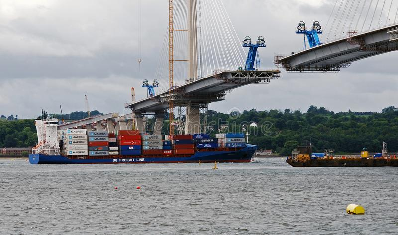 Container ship sailing under queensferry crossing stock photos