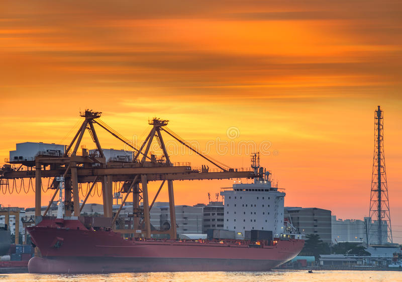 Container ships dock in Asia, while the loads are sky orange gold. stock image
