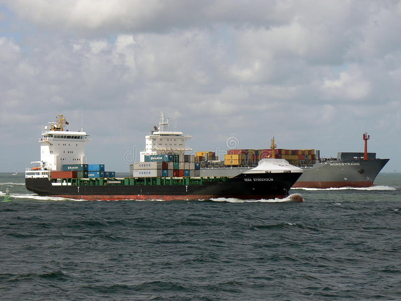 Container ships sailing towards port stock images