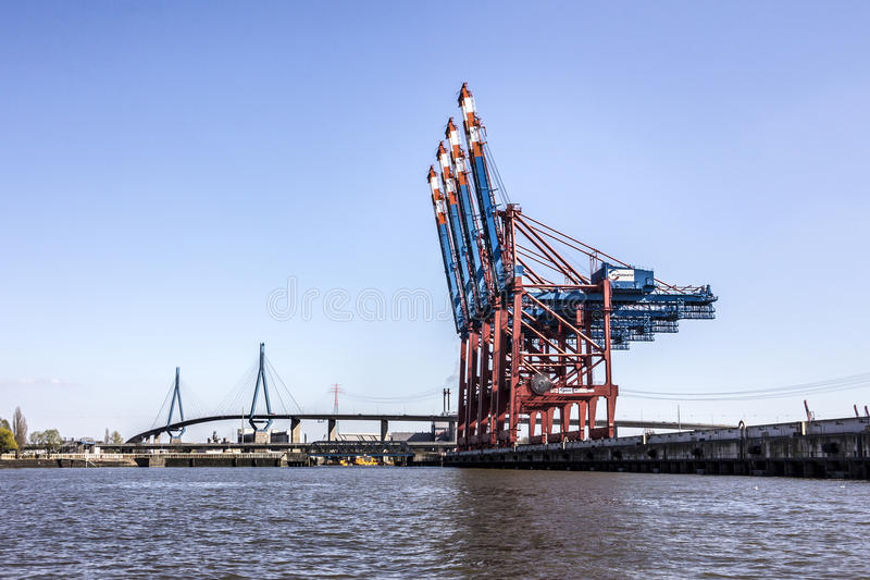 Container terminal. A container terminal in the harbor of hamburg, Germany. In the background is the elegantly curved Koehlbrand bridge. A ship lies not more royalty free stock photo