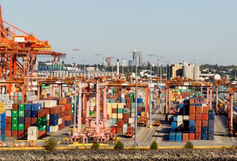 Container variopinti e gru arancio in porto fotografie stock libere da diritti