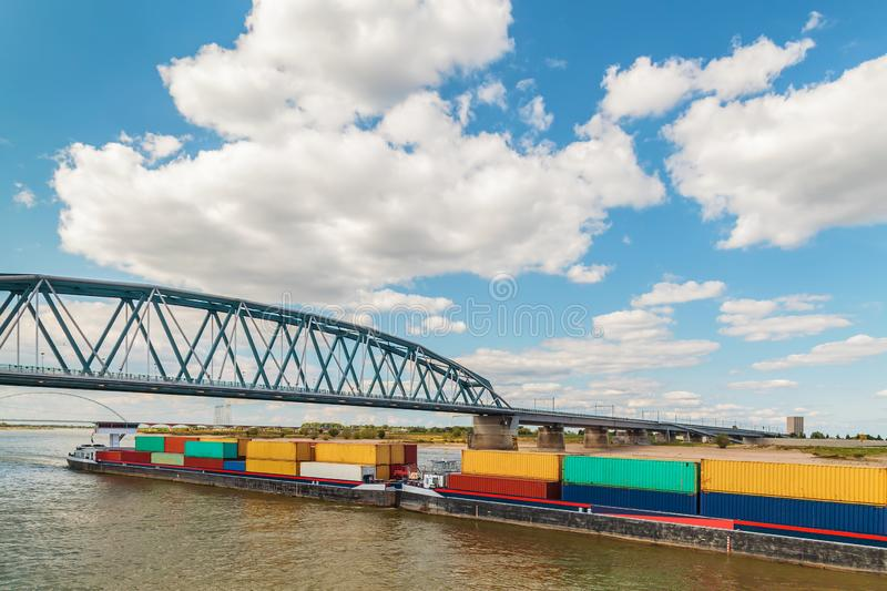 Container vessel passing a bridge on the Dutch river Waal in Nijmegen stock images