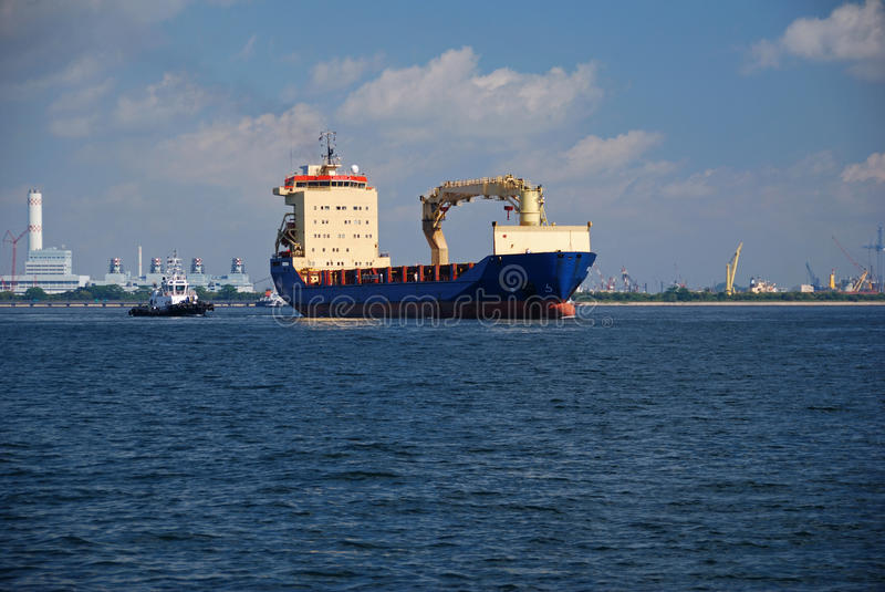 Container vessel transiting Singapore anchorage. Small blue container vessel passing through Singapore anchorage on her way to the container terminal stock image