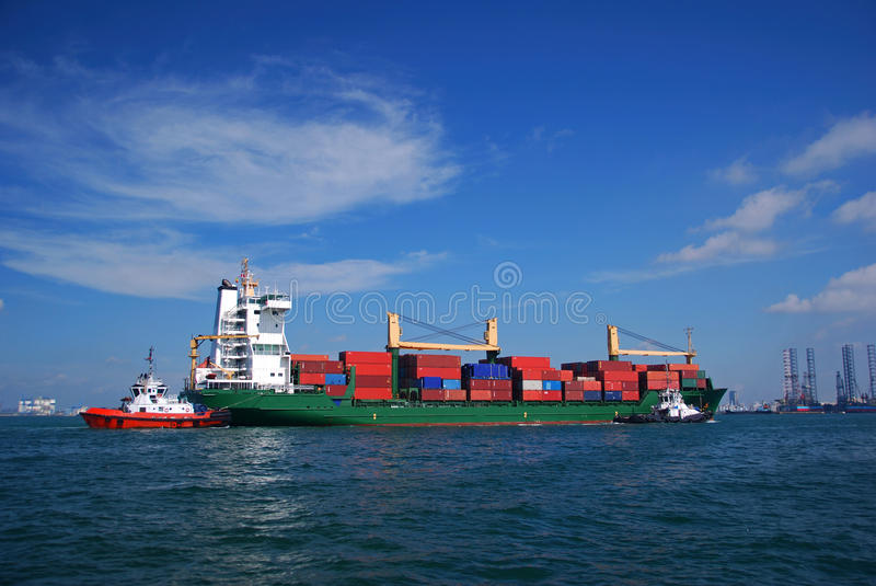 Container vessel transiting Singapore anchorage. Medium size almost fully loaded green container vessel passing through Singapore anchorage on her way to the stock photos