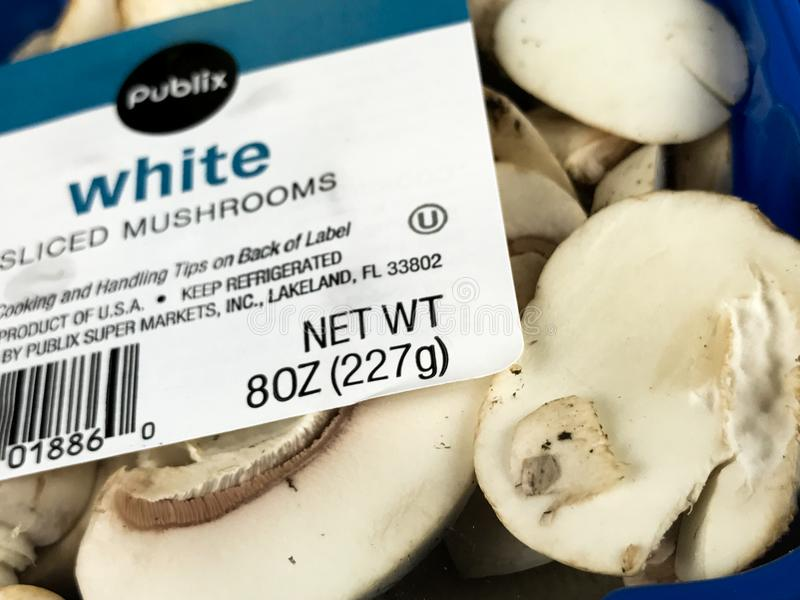 Container of White Sliced Mushrooms on a Black Backdrop stock photo