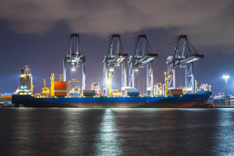 Containers die door grote kraan bij donkere zonsondergang laden, Verschepende Handelshaven stock afbeeldingen
