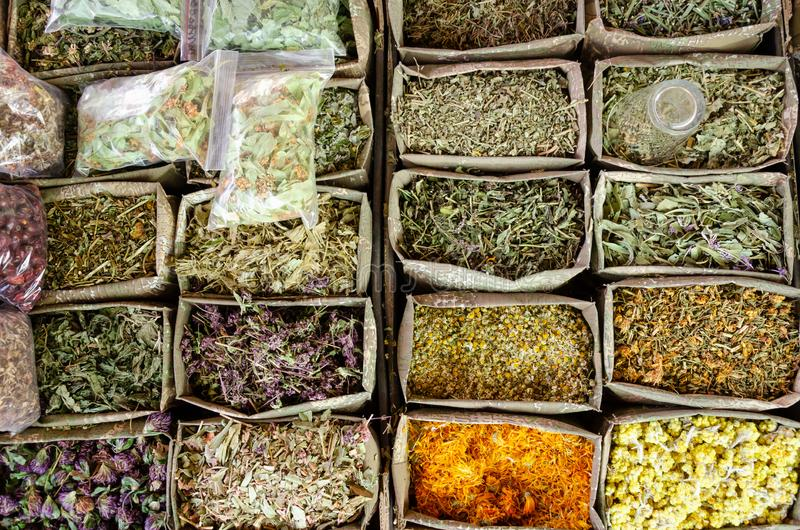 Containers with dried medicinal herbs for sale on the market. Healing herbs. Alternative medicine concept stock photo