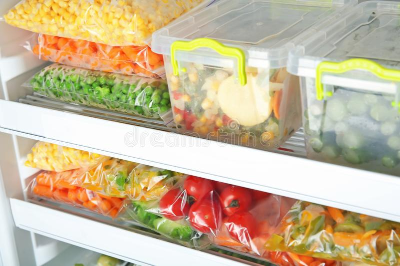 Containers and plastic bags with deep frozen vegetables. In refrigerator stock photography