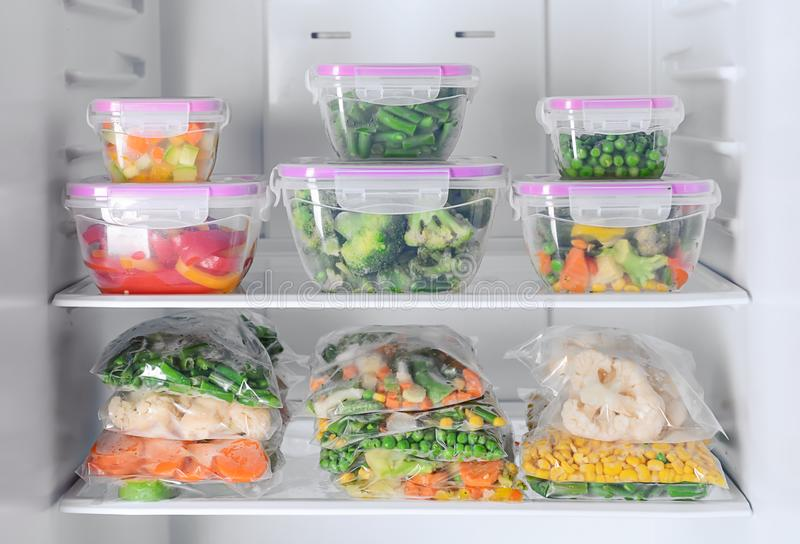 Containers and plastic bags with frozen vegetables in refrigerator stock images