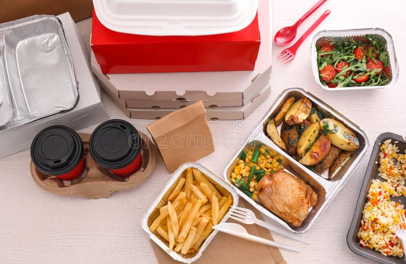 Containers with tasty takeout meals on light background, top view. Food delivery royalty free stock photo