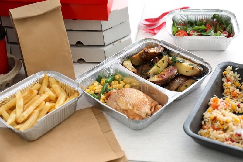Containers with tasty takeout meals on table. Food delivery royalty free stock photos