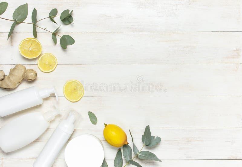 Containers van de wit leggen de Kosmetische fles, verse citroen, gemberwortel, eucalyptus op witte houten achtergrond hoogste men royalty-vrije stock foto's
