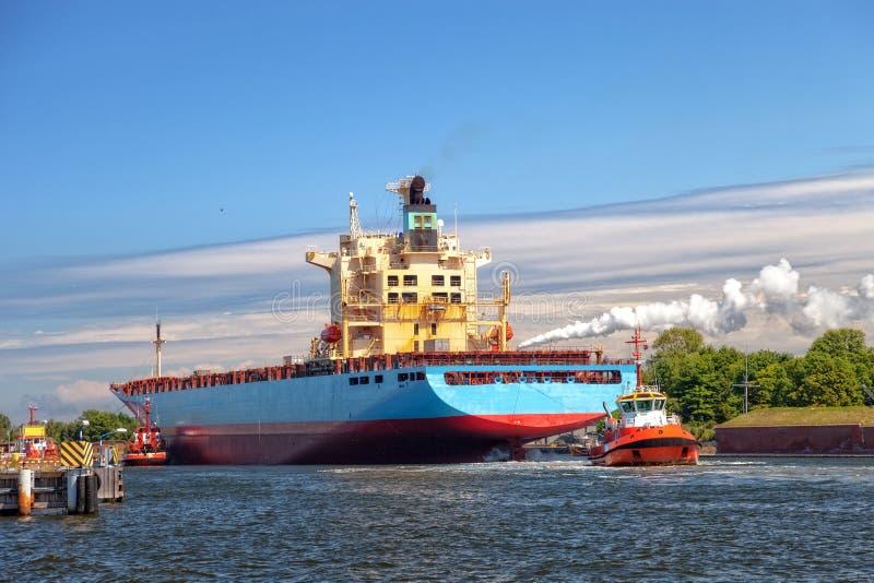 Containerschiff mit Schlepper stockfotos