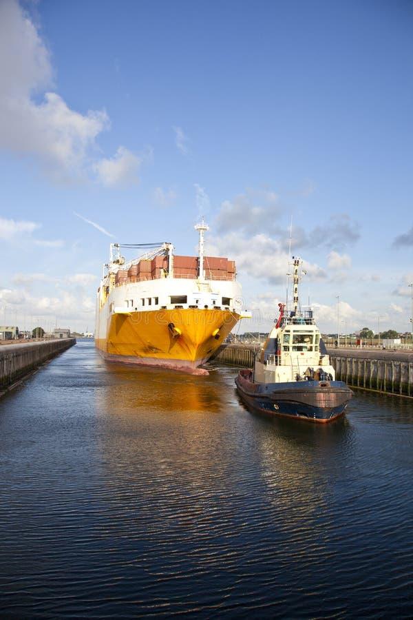 Containerschiff mit Schlepperboot in der Verriegelung stockbild