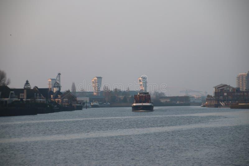Containerschip op Rivier Hollandse IJssen in het hol IJ van Capelle aan stock foto's
