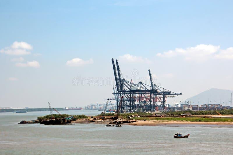 Containerterminal en containerschip op de Mekong rivier, Saigon-haven, Vietnam Weergeven van de pijlers en de kranen bij zonsopga royalty-vrije stock foto