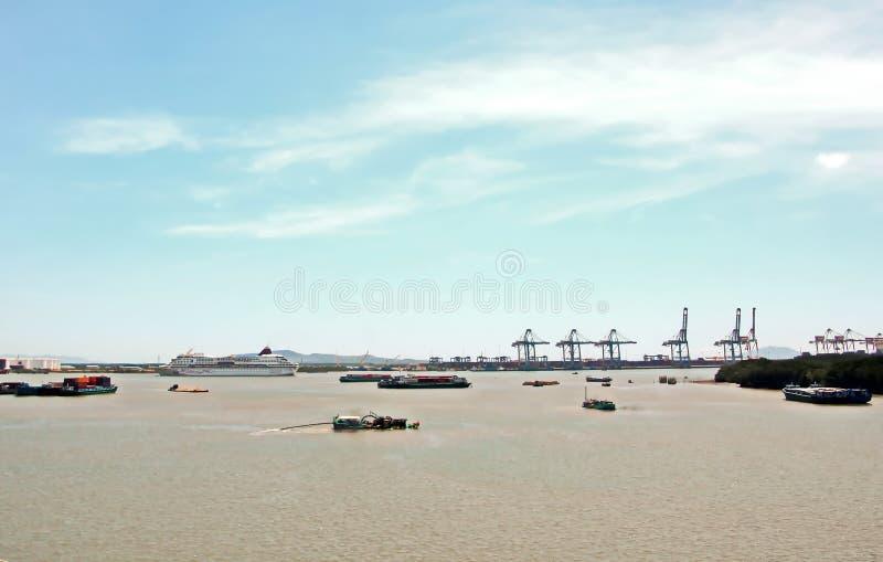 Containerterminal en containerschip op de Mekong rivier, Saigon-haven, Vietnam Weergeven van de pijlers en de kranen bij zonsopga stock afbeelding