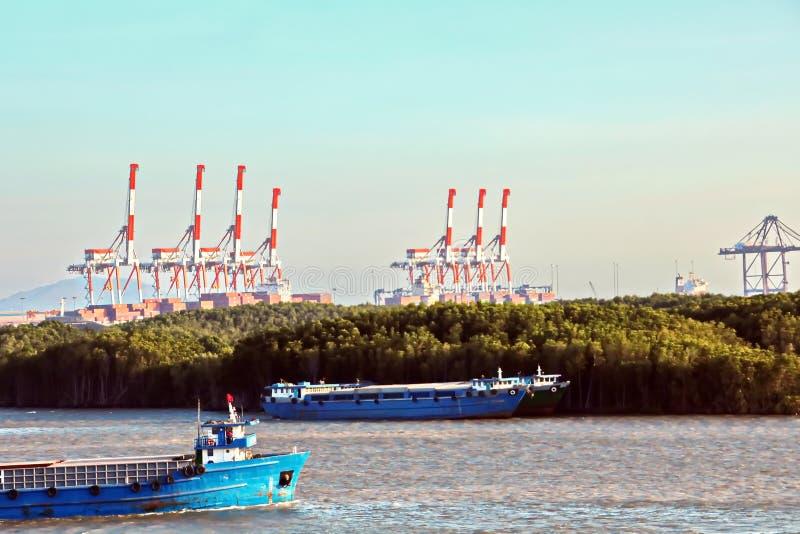 Containerterminal en containerschip op de Mekong rivier, Saigon-haven, Vietnam Weergeven van de pijlers en de kranen bij zonsopga royalty-vrije stock afbeelding