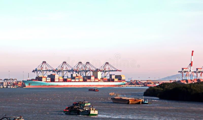 Containerterminal en containerschip op de Mekong rivier, Saigon-haven, Vietnam Weergeven van de pijlers en de kranen bij zonsopga stock afbeeldingen