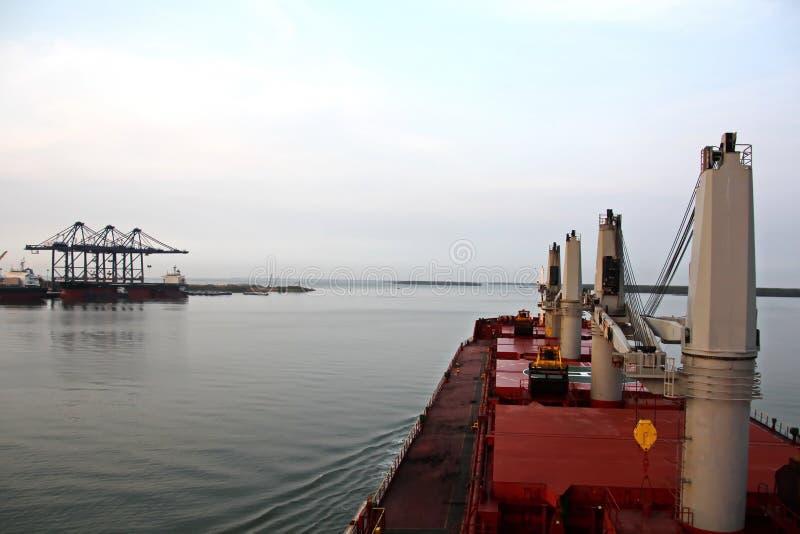 Containerterminal en containerschip op de Mekong rivier, Saigon-haven, Vietnam Weergeven van de pijlers en de kranen bij zonsopga royalty-vrije stock foto's