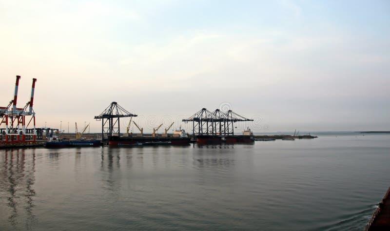 Containerterminal en containerschip op de Mekong rivier, Saigon-haven, Vietnam Weergeven van de pijlers en de kranen bij zonsopga stock foto's