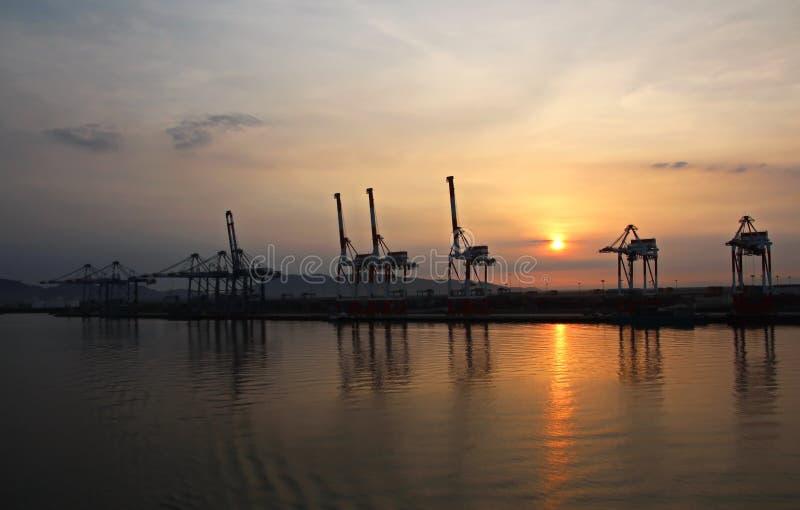 Containerterminal en containerschip op de Mekong rivier, Saigon-haven, Vietnam Weergeven van de pijlers en de kranen bij zonsopga royalty-vrije stock afbeeldingen