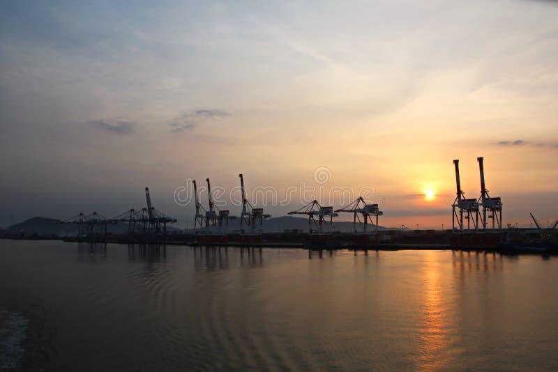 Containerterminal en containerschip op de Mekong rivier, Saigon-haven, Vietnam Weergeven van de pijlers en de kranen bij zonsopga royalty-vrije stock fotografie