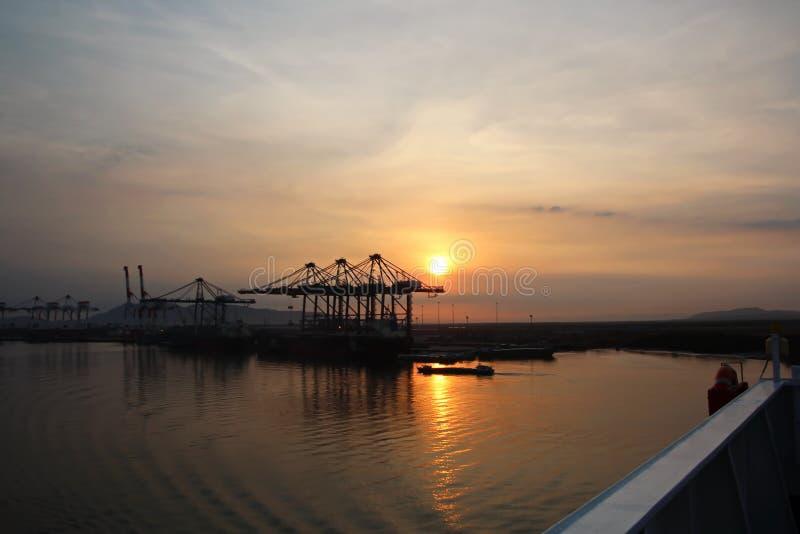 Containerterminal en containerschip op de Mekong rivier, Saigon-haven, Vietnam Weergeven van de pijlers en de kranen bij zonsopga stock fotografie