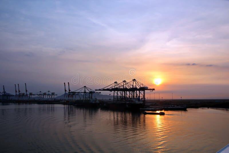 Containerterminal en containerschip op de Mekong rivier, Saigon-haven, Vietnam Weergeven van de pijlers en de kranen bij zonsopga stock foto
