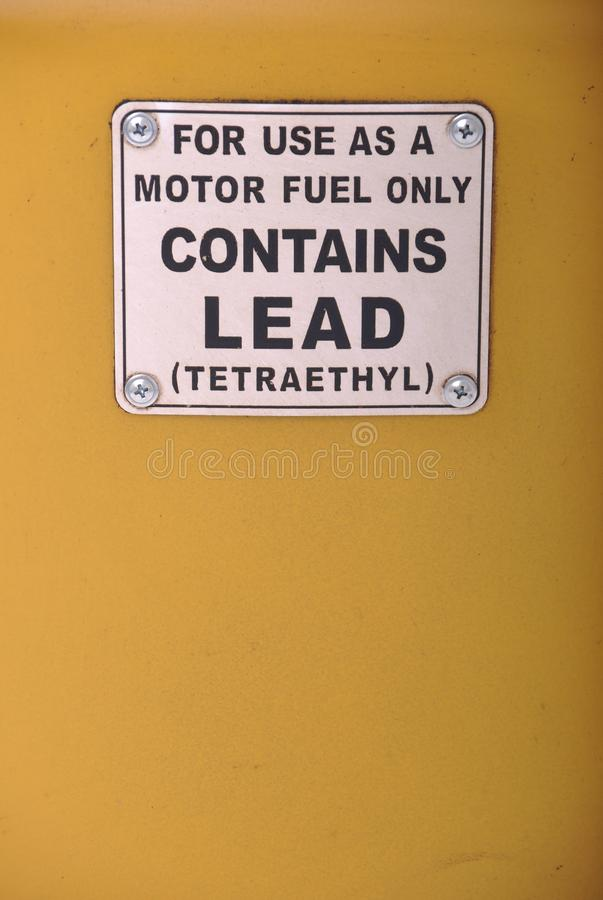 Contains lead sign. Contains lead vintage sign on a yellow gas pump background royalty free stock photo