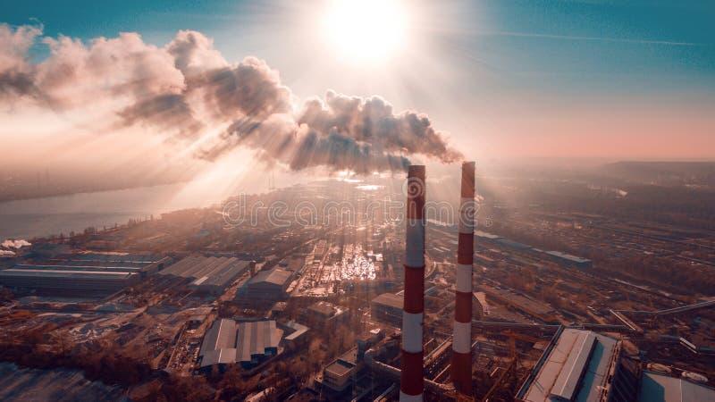 Contaminación atmosférica por el humo que sale de dos chimeneas de la fábrica Silueta del hombre de negocios Cowering fotografía de archivo libre de regalías