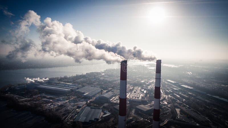 Contaminación atmosférica por el humo que sale de dos chimeneas de la fábrica Silueta del hombre de negocios Cowering imagenes de archivo