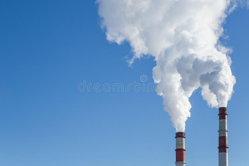Contaminación atmosférica Tubos con humo en el fondo del cielo azul imagen de archivo