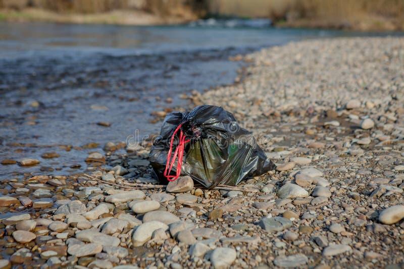 Contaminación cerca de la orilla, paquete cerca del río, residuos orgánicos plásticos del río de la basura, contribuyendo a la co foto de archivo libre de regalías