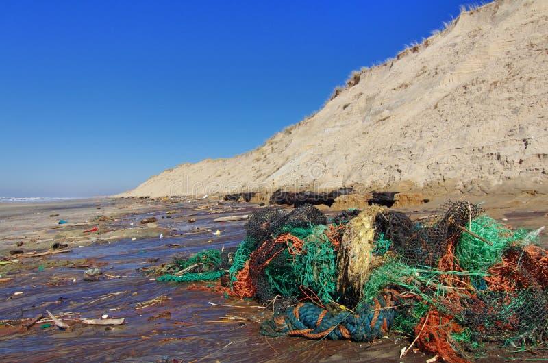Contaminación de la playa con los plásticos y las redes de pesca fotos de archivo