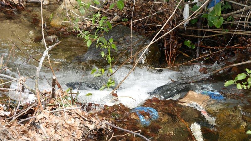 Contaminación del río de la montaña con la contaminación ecológica de la basura y de la basura plástica imagen de archivo libre de regalías