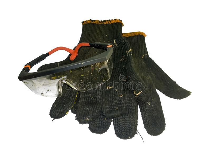 Contaminated glasses and gloves. Plastic glasses contaminated with small particles of cut grass on black soiled household gloves isolated on white background stock image