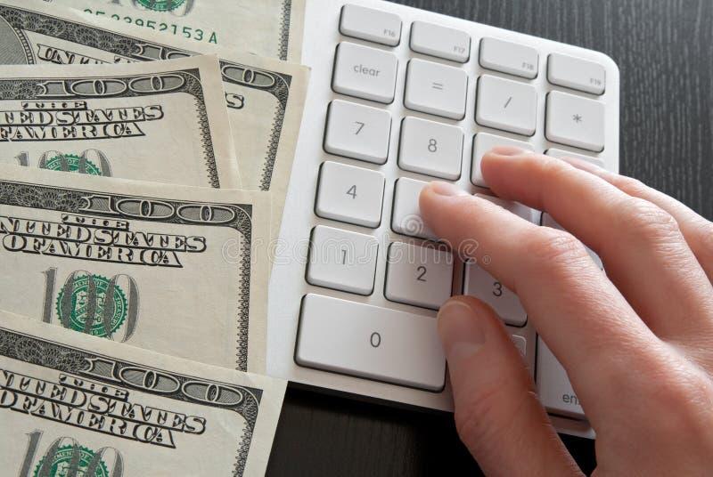 Contando o dinheiro na calculadora do computador fotos de stock royalty free