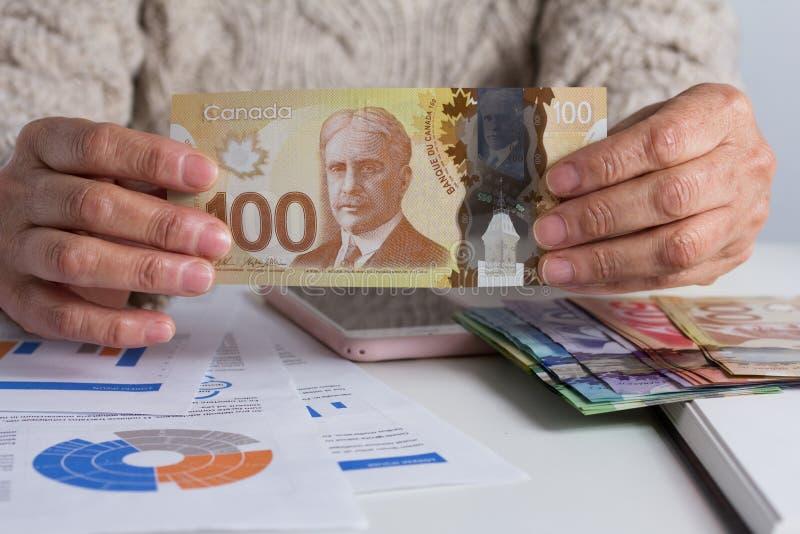 Contant geldrekeningen van Canadese munt Dollars De teruggetrokken rekening van de vrouwenholding op bureaubureau stock foto's