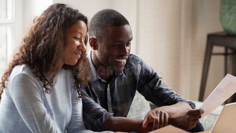 Contas de papel da verificação feliz dos pares da raça misturada que pagam em linha foto de stock royalty free