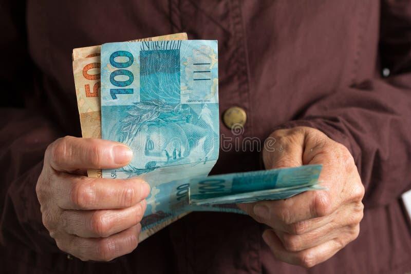 Contas do dinheiro da moeda brasileira Pessoa aposentada idosa que paga dentro foto de stock
