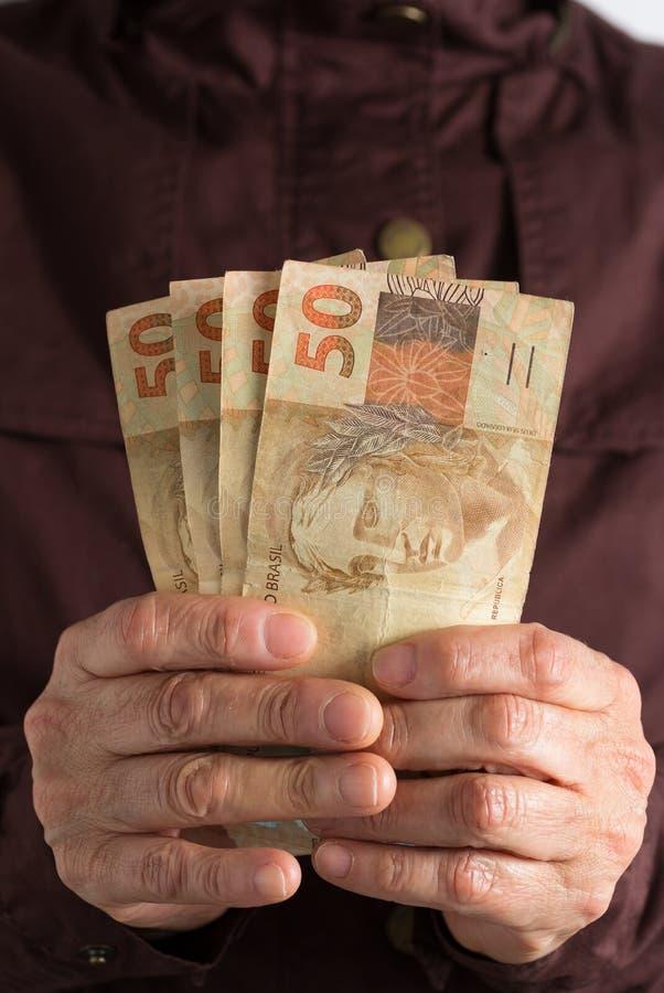 Contas do dinheiro da moeda brasileira Pessoa aposentada idosa que paga no dinheiro imagem de stock royalty free