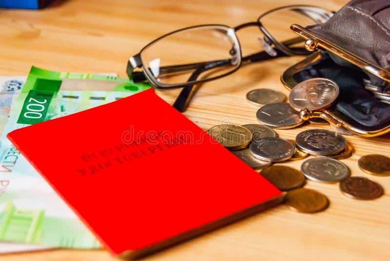 Contas e moedas pequenas, uma bolsa aberta e vidros ao lado do pensioner& x27; o certificado de s está na tabela imagens de stock royalty free